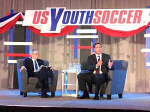 Paul Caligiuri (right) addresses the crowd at a US Soccer presidential candidate forum put on by US Youth Soccer at the 2018 United Soccer Coaches Convention in Philadelphia. Photo: Chris Moore, US Youth Soccer