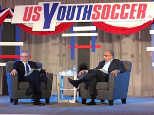 Carlos Cordeiro (right) answers a question from moderator JP Dellacamera at a US Soccer presidential candidate forum put on by US Youth Soccer at the 2018 United Soccer Coaches Convention in Philadelphia. Photo: Chris Moore, US Youth Soccer