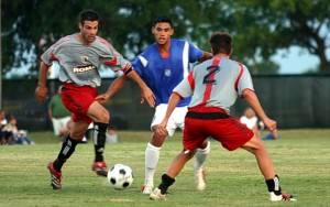 Dominic Schell of Dallas Roma FC dribbles the ball against Miami FC during the 2006 US Open Cup Second Round match as teammate Beau Brown (No. 2) looks on. Photo: Dallas Roma FC