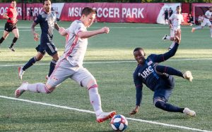 Alex Muyl of the New York Red Bulls has his shot blocked by Luis Caicedo of the New England Revolution in the Fourth Round of the 2019 US Open Cup. Photo: Bob Larson