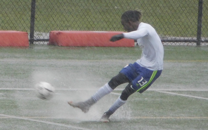A Brockton FC United player strikes the ball in the heavy rain in the club's 2020 US Open Cup qualifier against the New York Pancyprian Freedoms. Photo: Liz McQuilkin - Mass Soccer